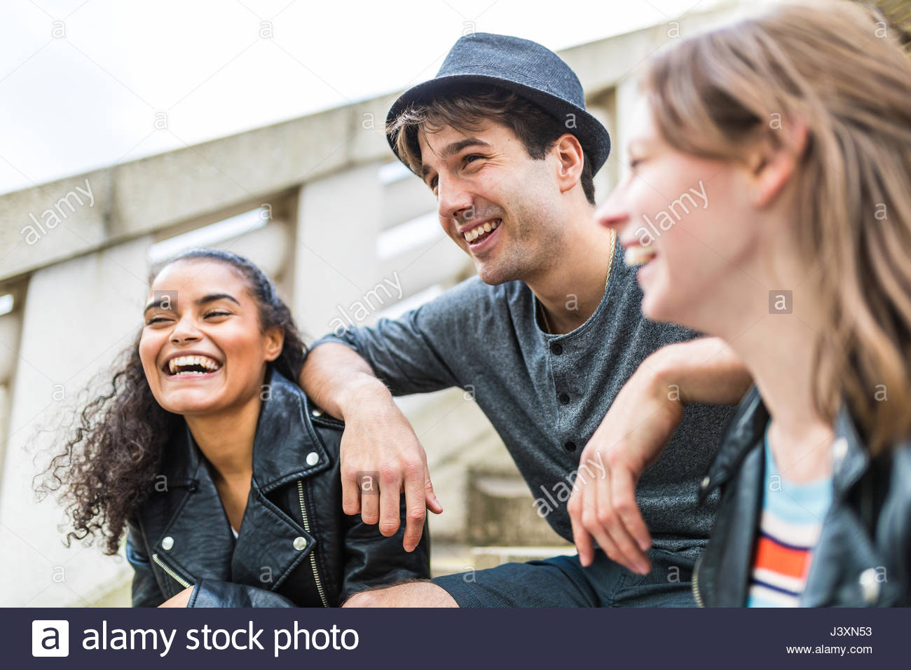 Drei junge erwachsene Freunde auf eine Treppe in Battersea Park chatten Stockbild