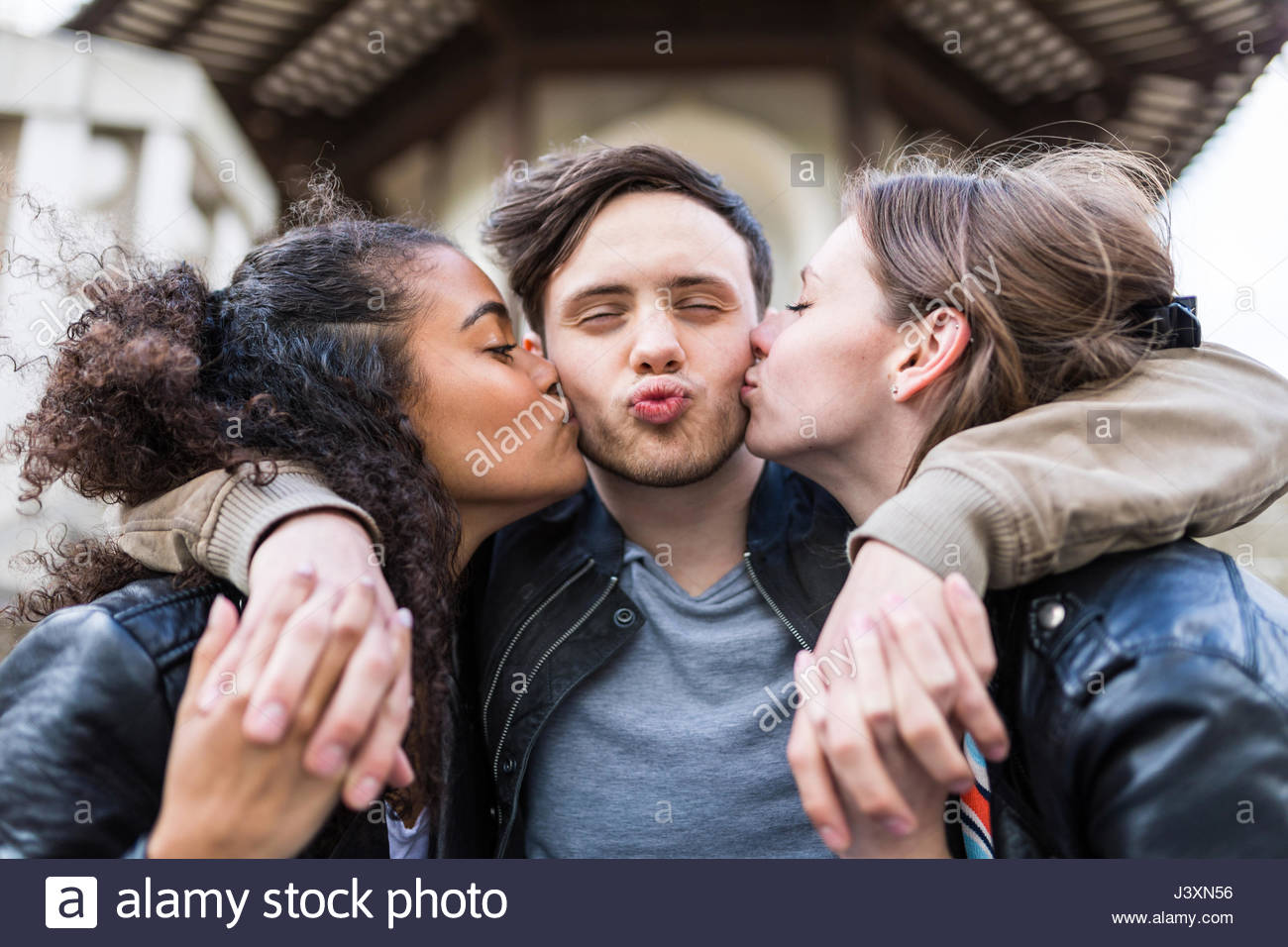 Junger Mann zwischen zwei Frauen ihn Küssen auf die Wange in Battersea Park Stockbild