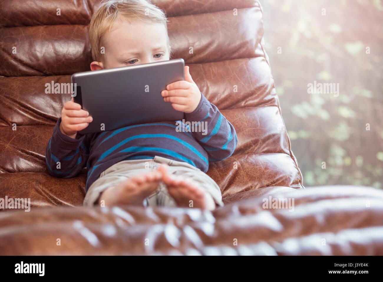 Kleinkind Jungen liegend auf Stuhl Blick auf tablet Stockbild