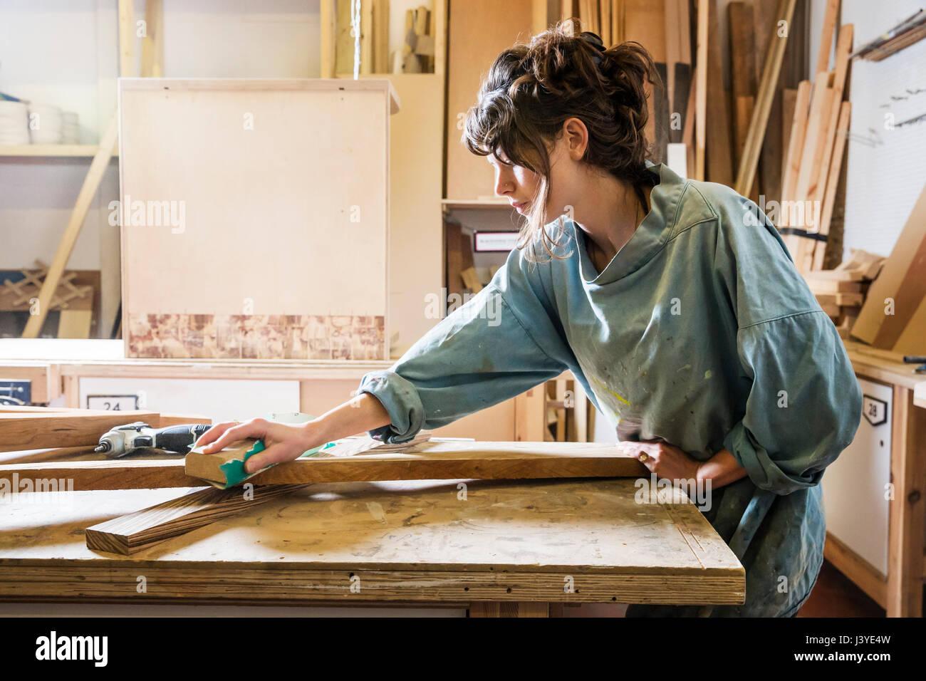 Junge Frau Schleifen Holz in einem workshop Stockbild
