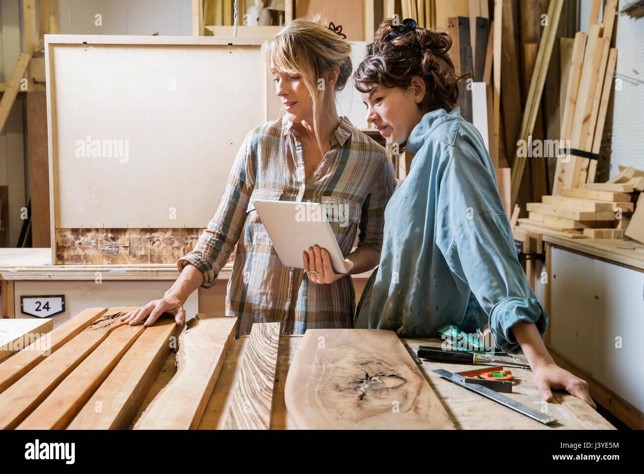 Zwei Frauen, die Wahl von Holz aus einer Auswahl in einem Workshop Beratung auf einem tablet Stockbild