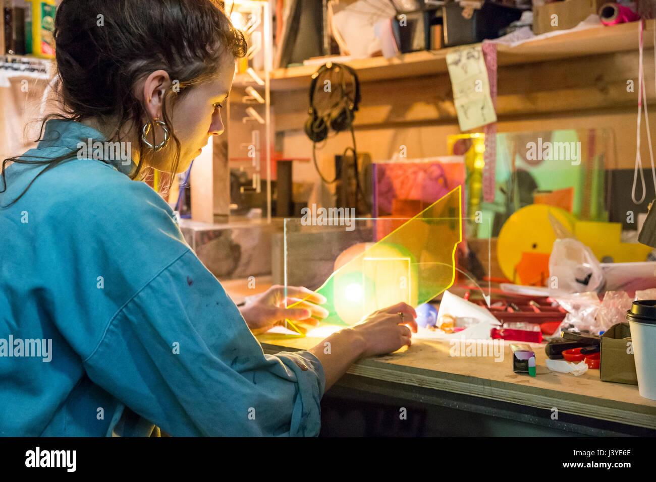 Junge Frau betrachten Materialien in einem Handwerksbetrieb Stockbild