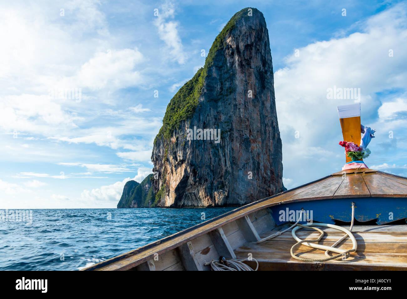 Longtail-Boot im Meer gegen blauen Himmel und Insel Stockfoto