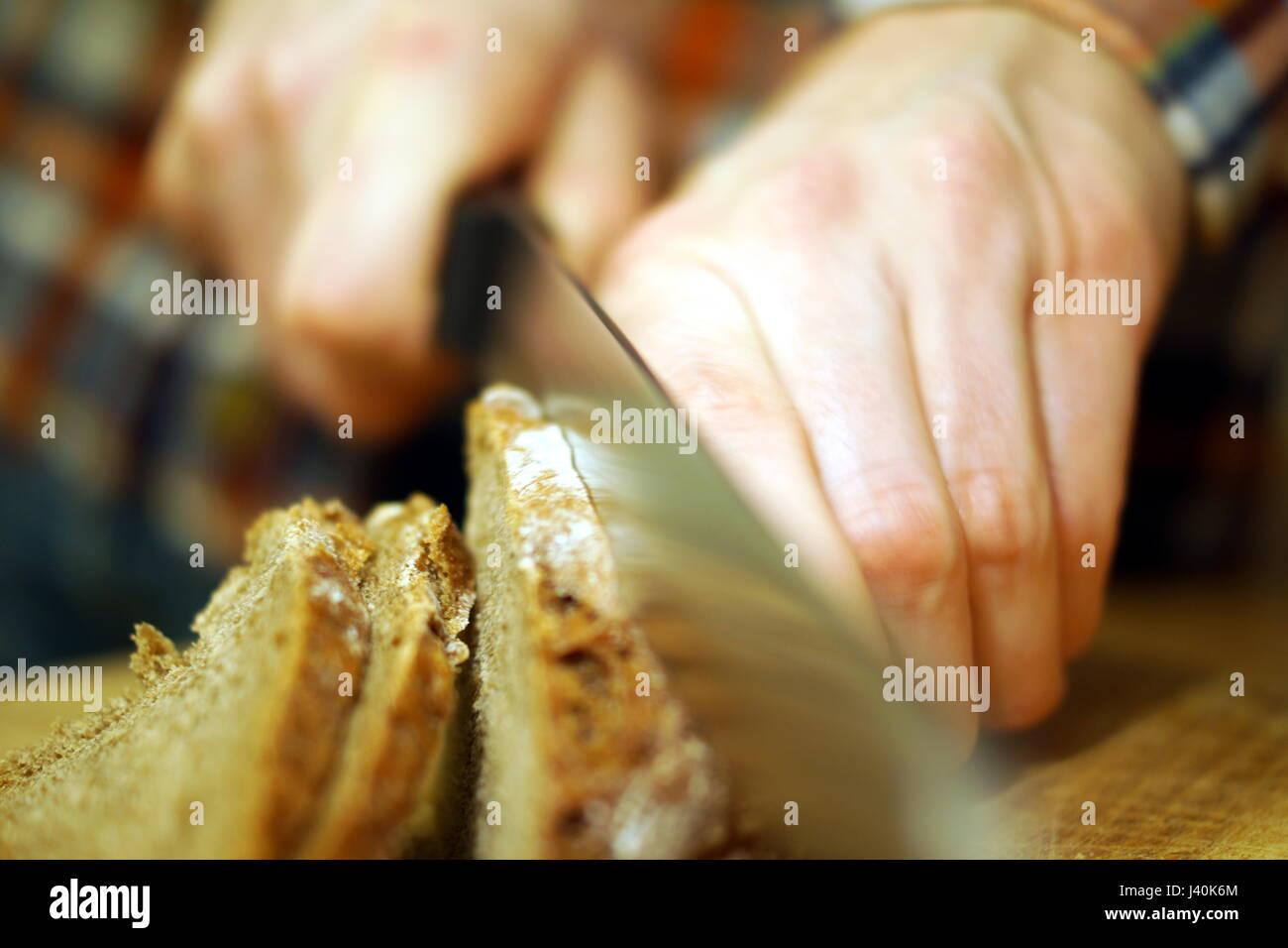 Schneiden von Brot mit einem Messer Stockbild