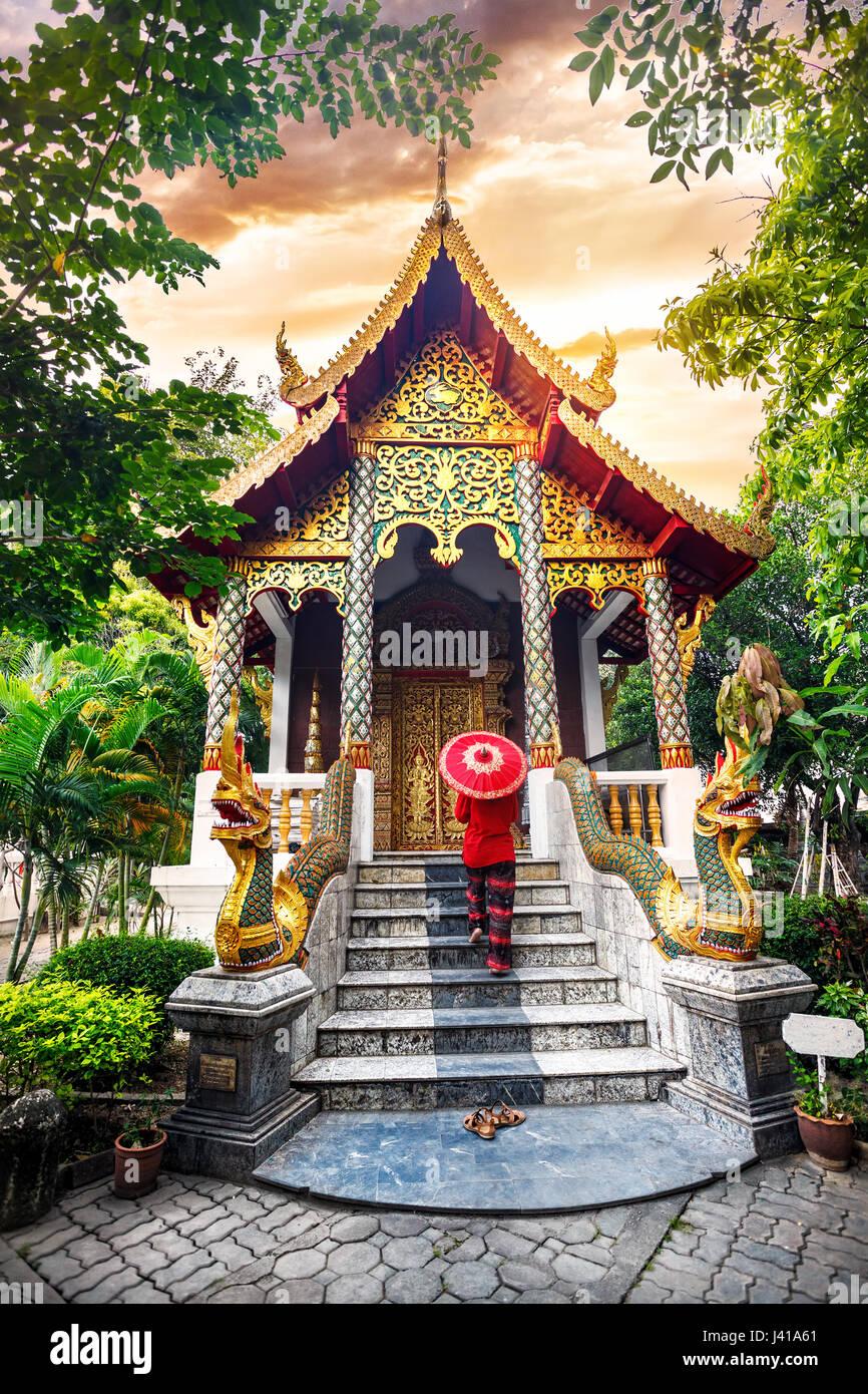 Frau Tourist mit roten traditionelle Thai Regenschirm im Tempel Kloster mit Drachen Statuen am Sonnenuntergang Himmel Stockbild