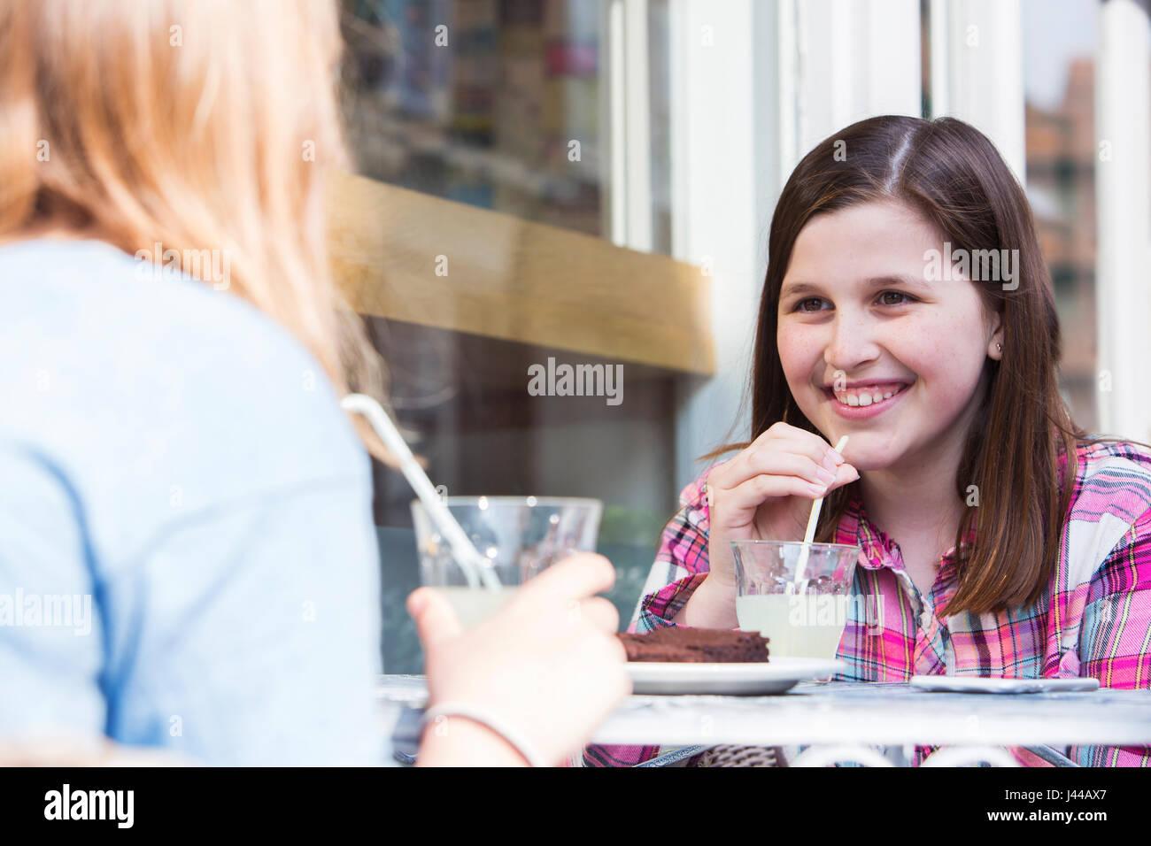 Zwei junge Mädchen im Chat am Café im freien Tisch Stockbild