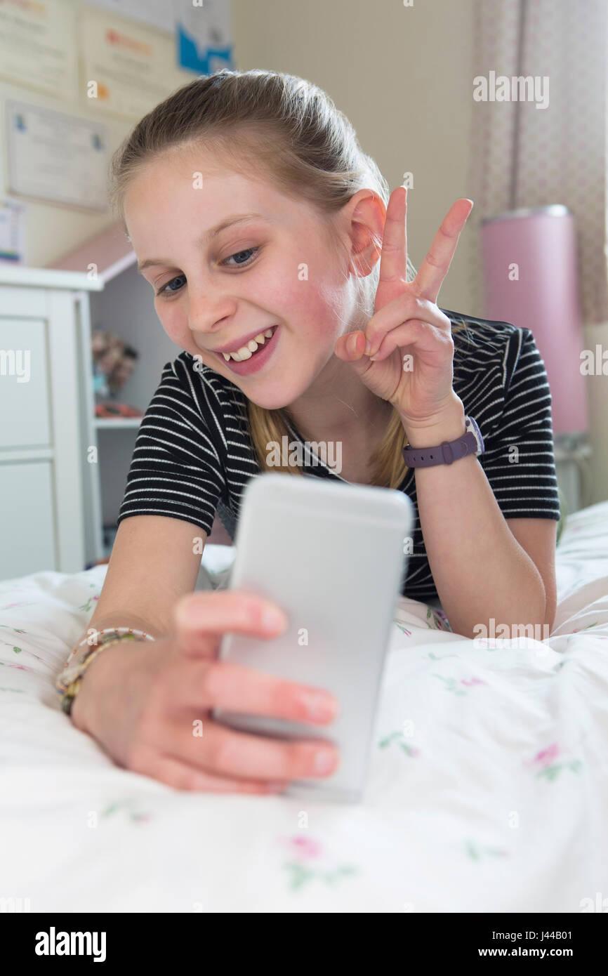 Junges Mädchen posieren für Selfie im Schlafzimmer Stockfoto