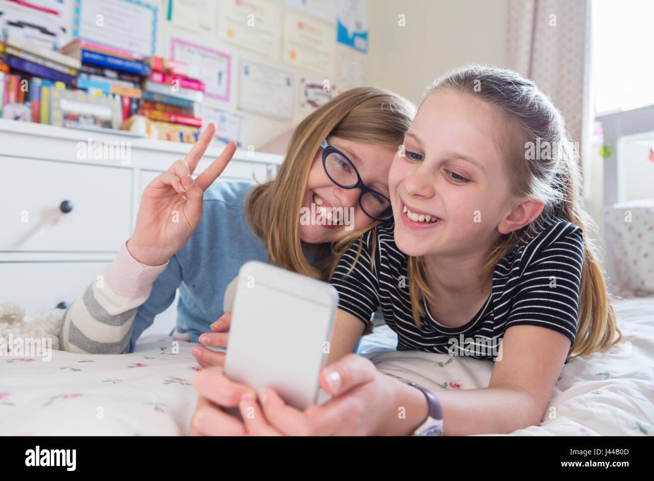 Zwei junge Mädchen posieren für Selfie im Schlafzimmer Stockbild