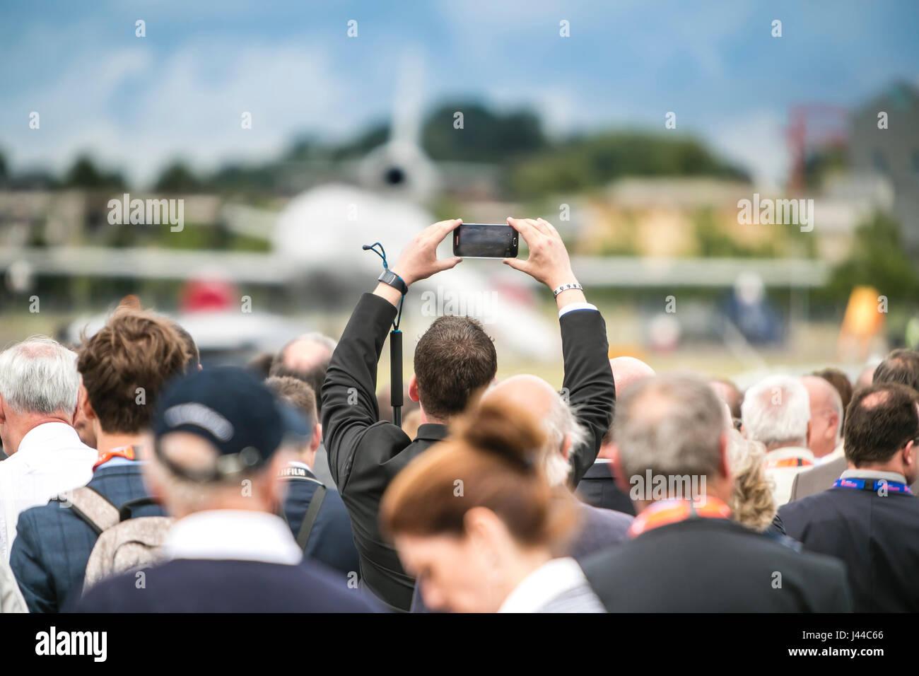 Zuschauer nehmen selfie bei Air Show mit dem Flugzeug im Hintergrund Stockbild