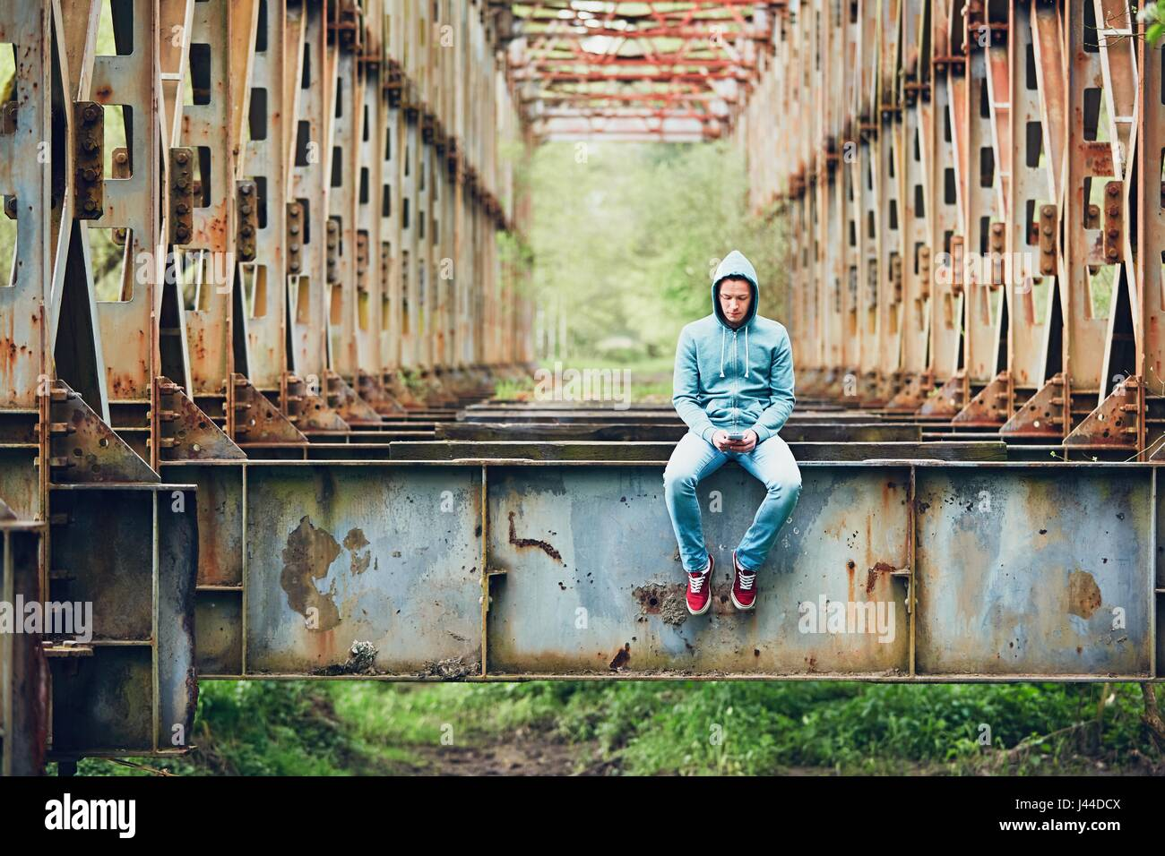 Trauriger Mann mit Handy auf der verlassenen rostigen Brücke. Konzept für Traurigkeit, Einsamkeit, Verbindung und Stockfoto
