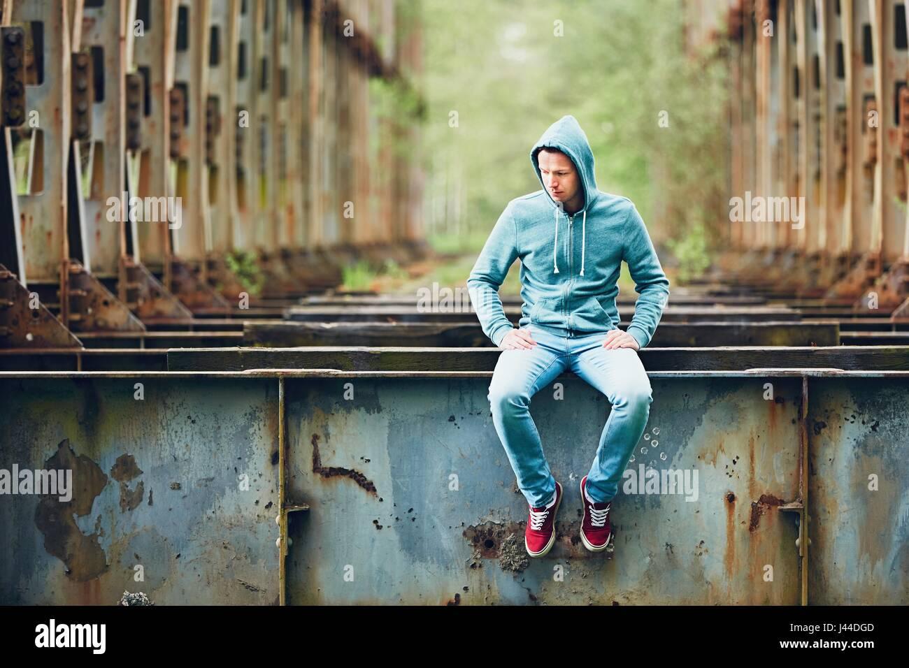 Trauriger Mann sitzt auf der verlassenen rostigen Brücke. Konzept für Traurigkeit, Einsamkeit und vieles Stockbild