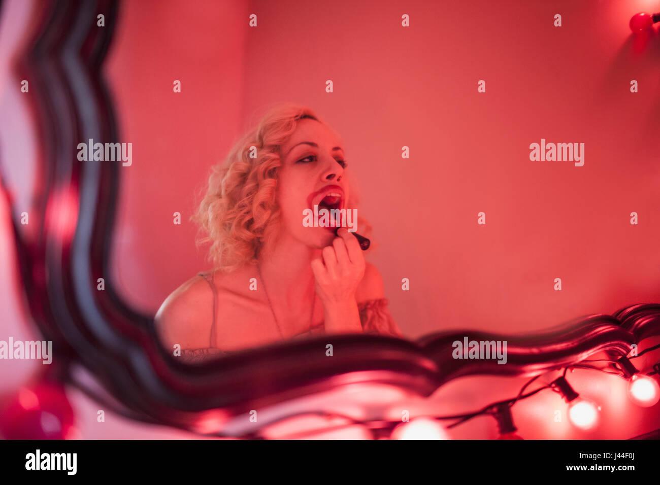 Eine junge Frau, Auftragen von Lippenstift in einem Spiegel. Stockbild