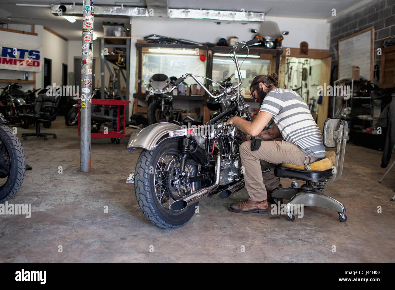 Junger Mann, ein Motorrad zu reparieren Stockbild