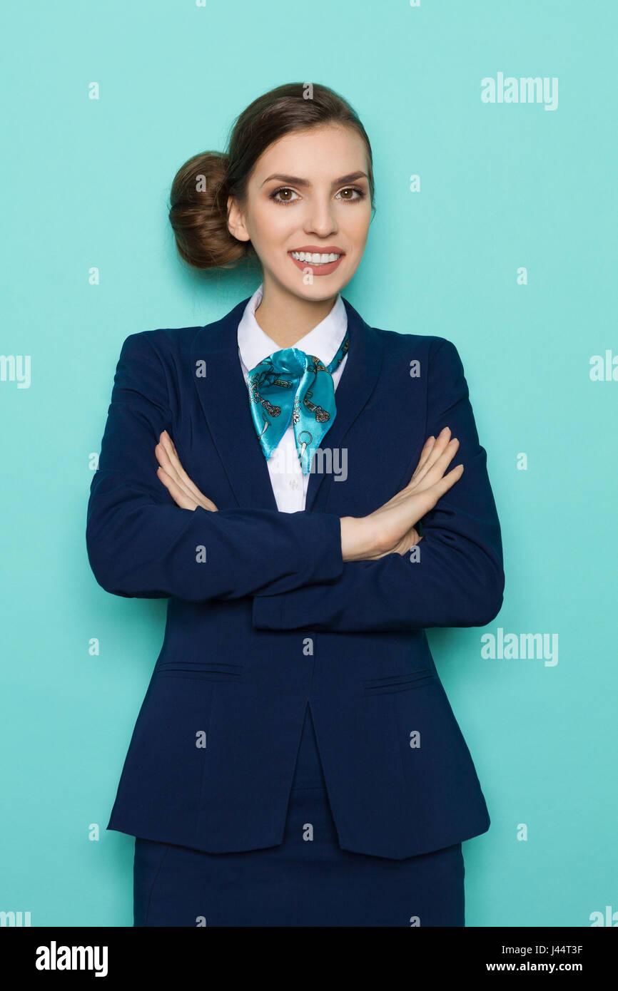 Lächelnde junge Geschäftsfrau im blauen Anzug und Türkis Schal steht mit verschränkten Armen Stockbild