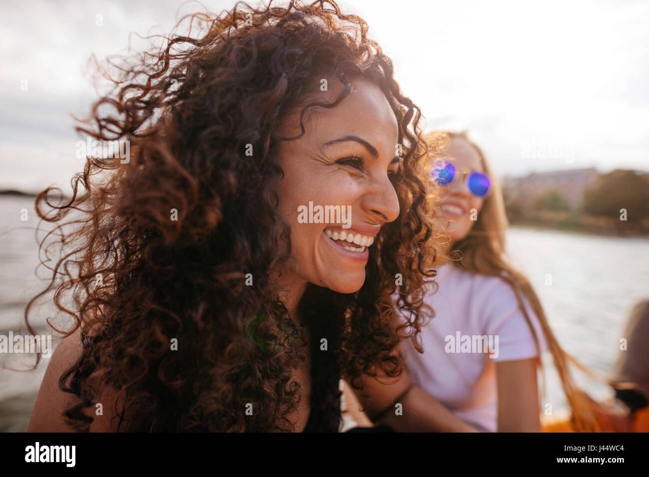 Schuss der fröhliche junge Frau im Freien mit Freundin im Hintergrund hautnah. Stockfoto