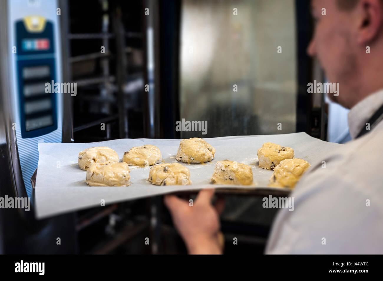 Ein Koch stellt ein Tablett mit Scones in einen Ofen Küche Essen kochen backen Essen im Restaurant Vorbereitung Stockbild