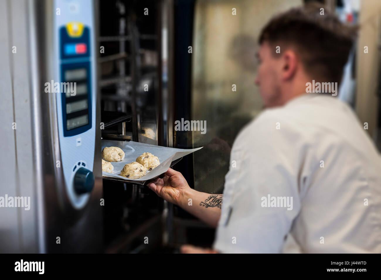 Koch stellt ein Tablett mit Scones in einem Ofen; Küche; Essen; Kochen; Backen; Restaurant; Zubereitung von Stockbild