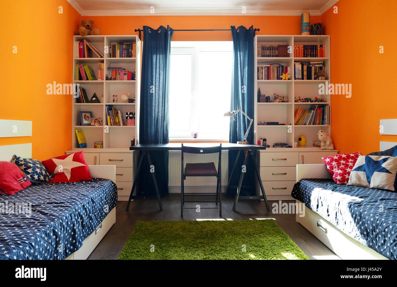 Kinderzimmer mit zwei Betten und Regale in orange und blau ...