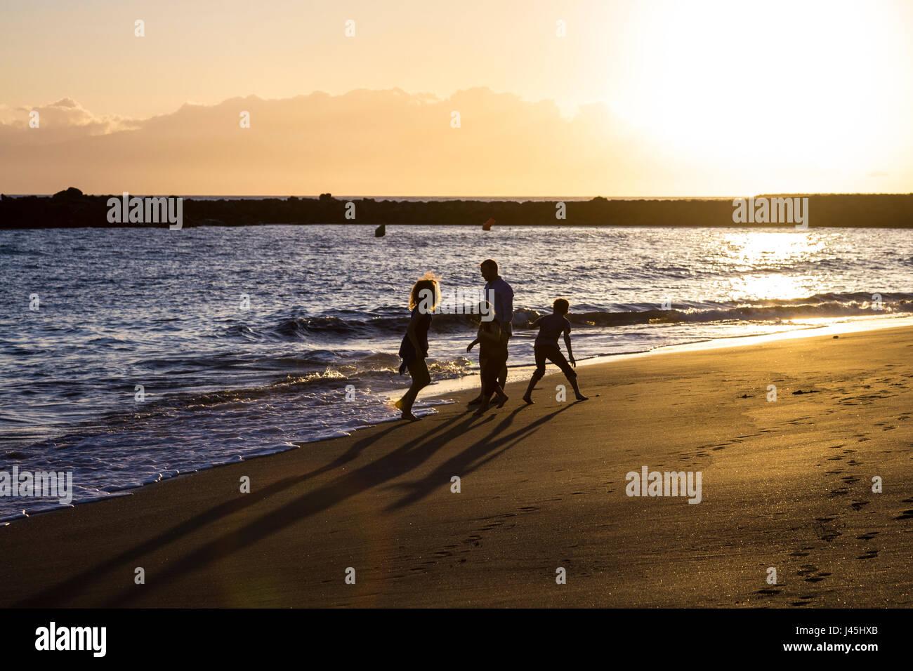 Silhouetten von einer Familie am Strand bei Sonnenuntergang (Teneriffa, Spanien) Stockbild