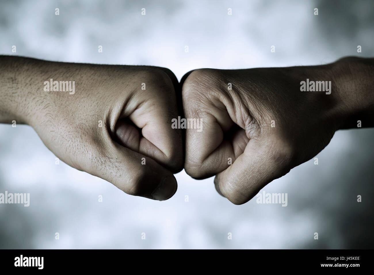 Nahaufnahme von den Händen der zwei jungen kaukasischen Männer, die ihre Fäuste stoßen Stockbild