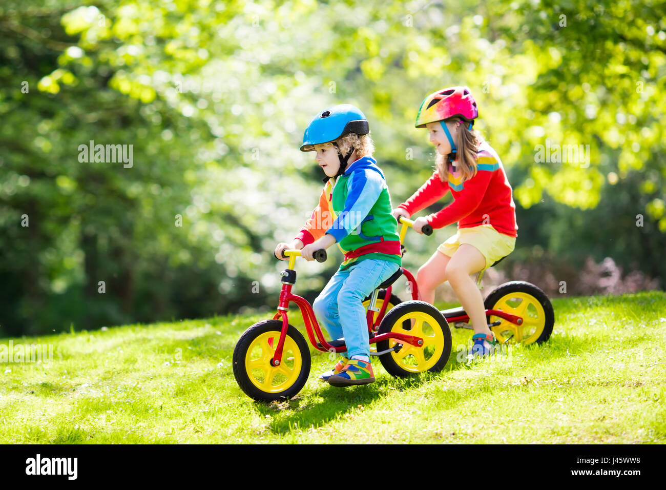 kinder laufrad fahren kinder auf dem fahrrad im sonnigen. Black Bedroom Furniture Sets. Home Design Ideas