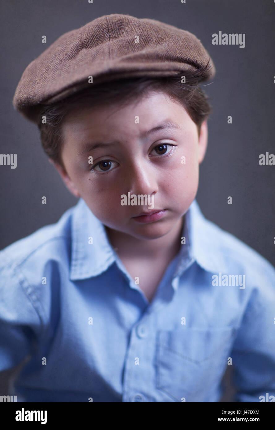 Süß und ernsthafte Suche multi-ethnischen asiatische Kaukasischen kleiner Junge trägt ein blaues Poloshirt und braunem Stockfoto