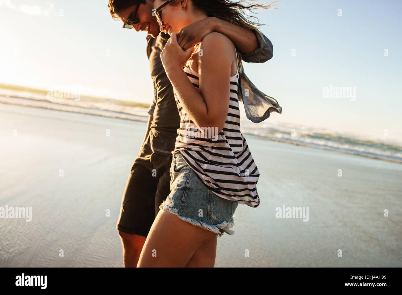 Im Freien Schuss des jungen Paares zu Fuß am Strand. Junger Mann und Frau zusammen spazieren am Strand an einem Stockbild