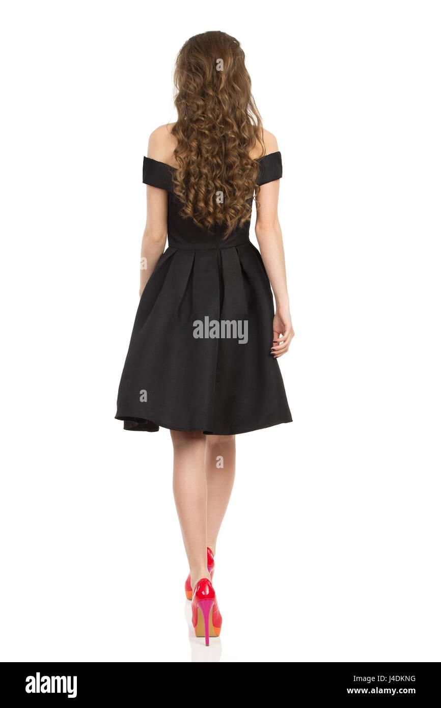 Junge Frau im eleganten schwarzen Cocktailkleid und roten high Heels ...