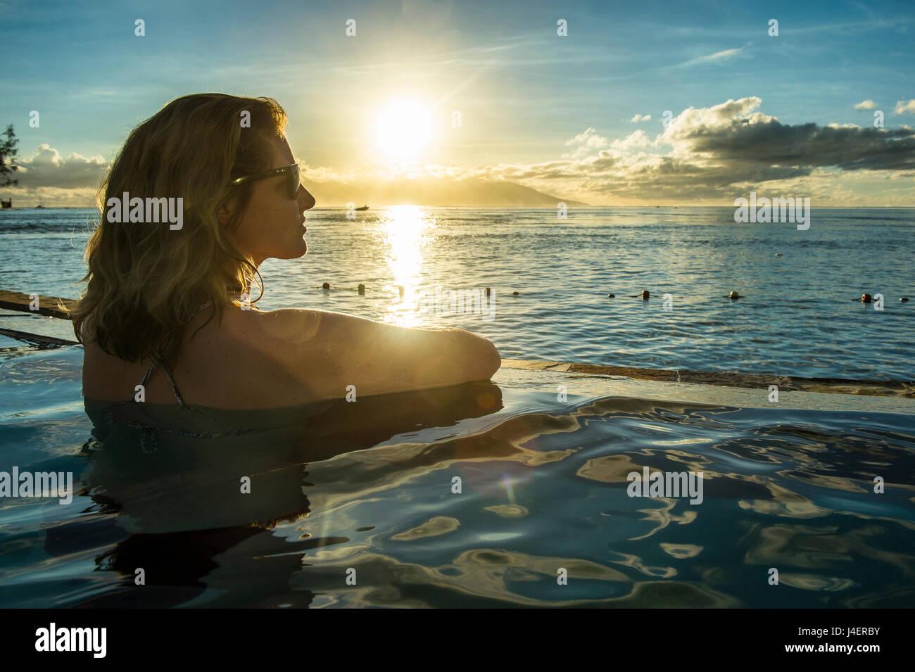 Frau, genießen den Sonnenuntergang in einem Schwimmbad mit Moorea in den Hintergrund, Papeete, Tahiti, Gesellschaftsinseln Stockbild