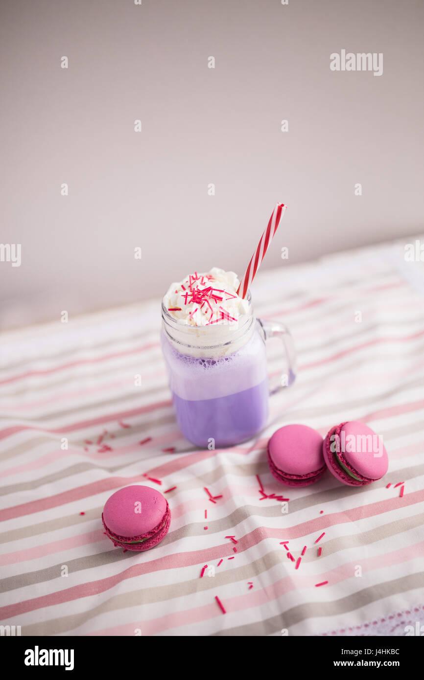 Lila Kaffee in Tasse stilisierte Einmachglas mit Macarons und Rosen und bunte Dekoration. Heidelbeer-Milch-Shake. Stockbild