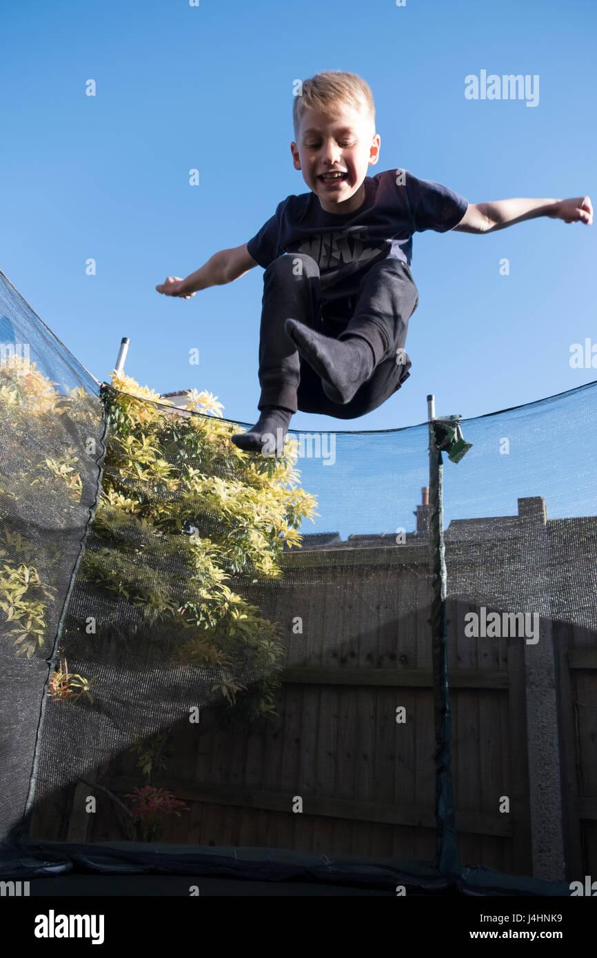 Kleiner junge Spaß springen auf einem Trampolin in seinem Garten Stockbild