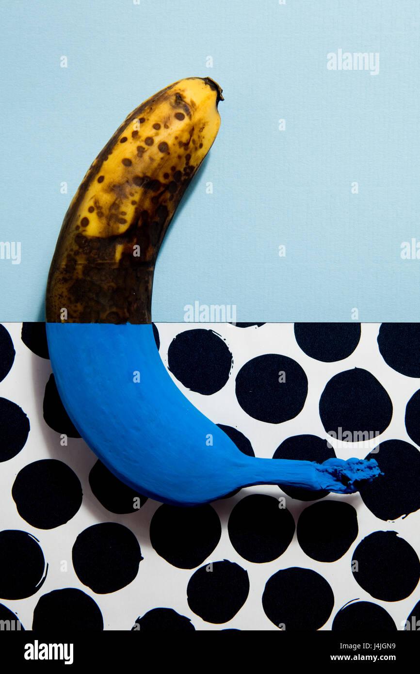 Eine Hälfte lackiert Banane blau jeweils die Hälfte gegen die einfarbigen Hintergrund und Punkte Stockbild