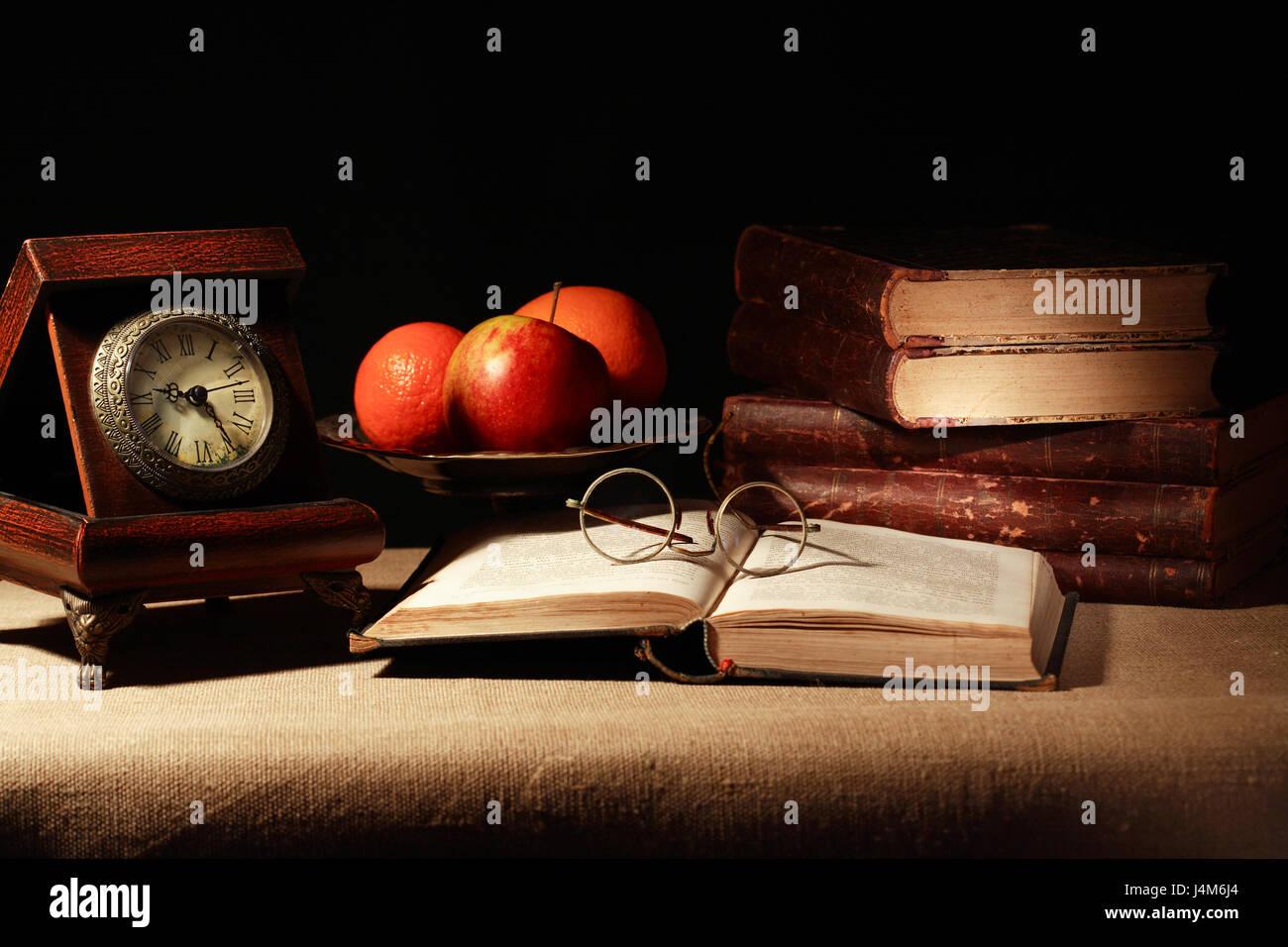 Vintage Stil Leben mit alte Uhr, in der Nähe von Obstschale und Buch auf dunklem Hintergrund Stockbild