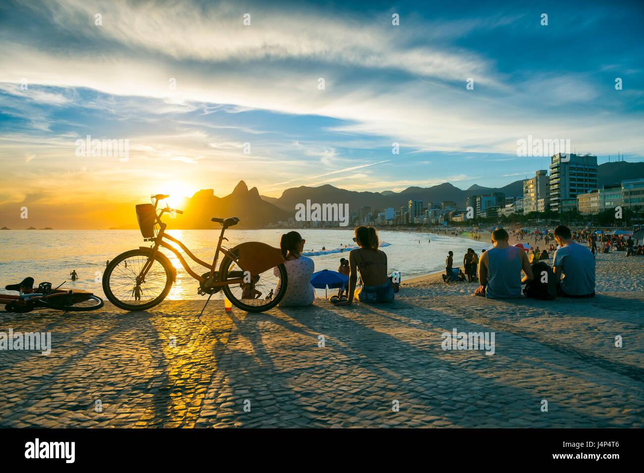 Leute sitzen, den Sonnenuntergang am Arpoador, eine beliebte Sommer-Aktivitäten für Einheimische und Touristen, Stockbild