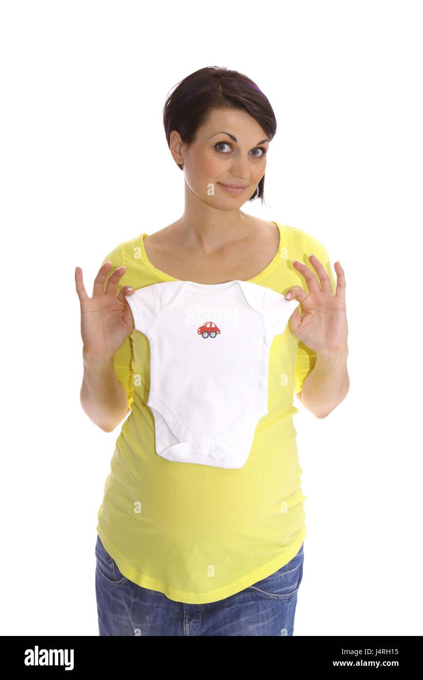 Schwangere Frau in glücklich Erwartung zeigt Baby-Bekleidung, Modell veröffentlicht Stockbild
