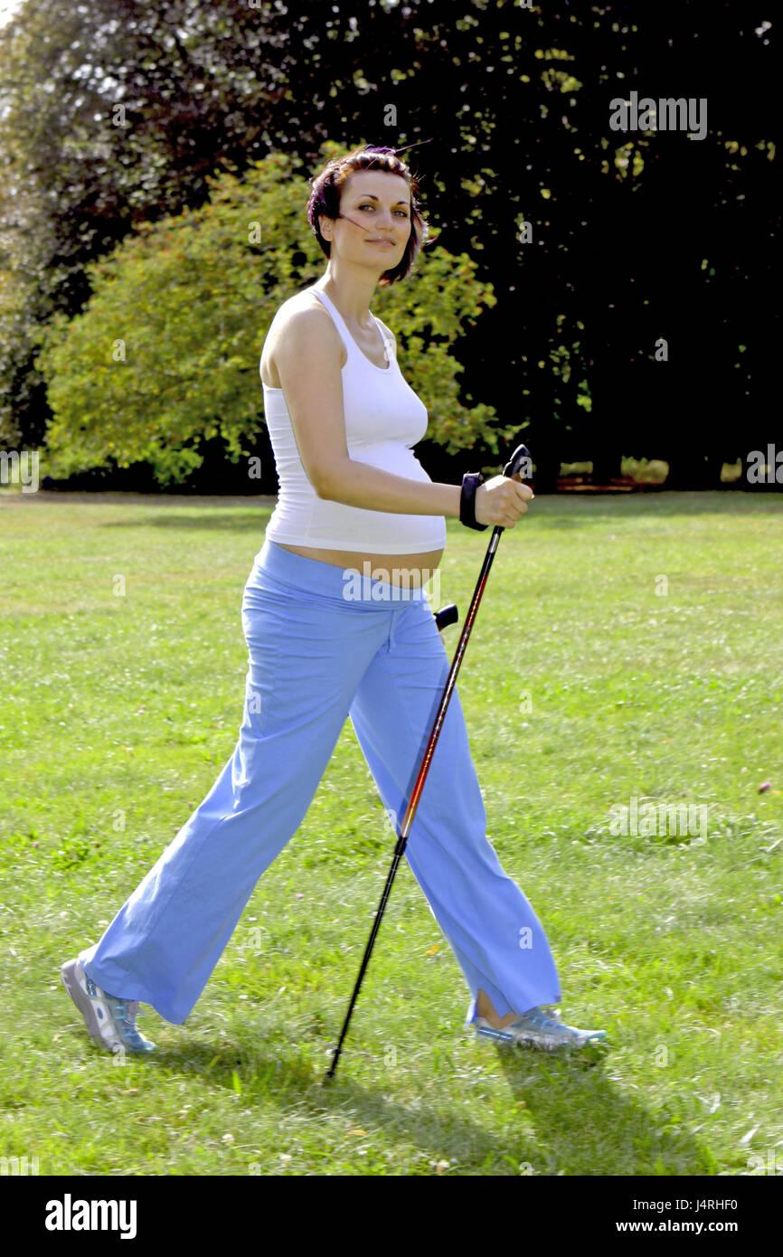 Schwangere Frau im Sommer hält sich Fit mit Nordic Walking, Modell veröffentlicht, Stockbild