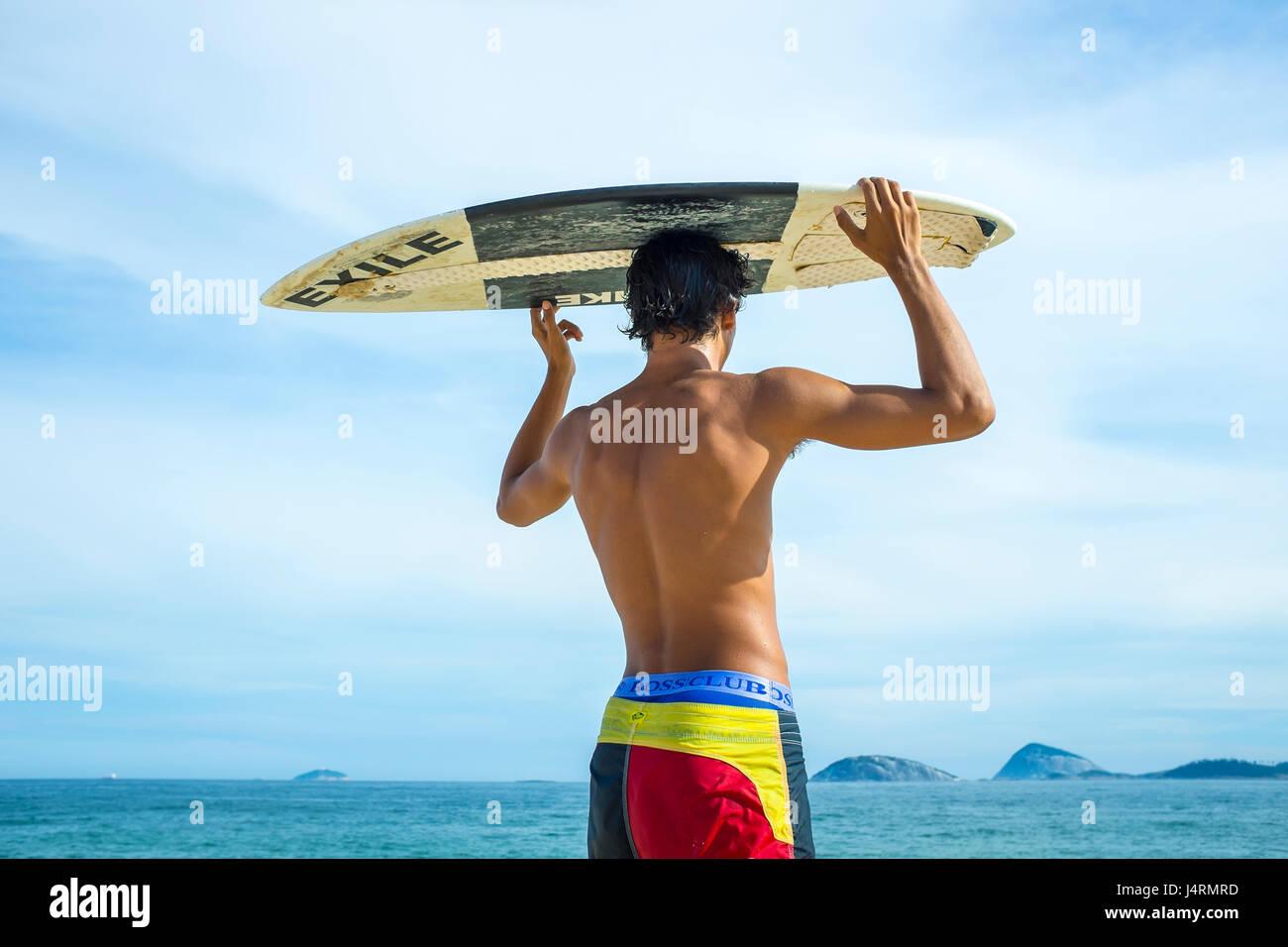 RIO DE JANEIRO - 5. Februar 2017: Ein junger steht Brasilianer Scannen für Wellen mit seinem Skimboard über Kopf Stockfoto