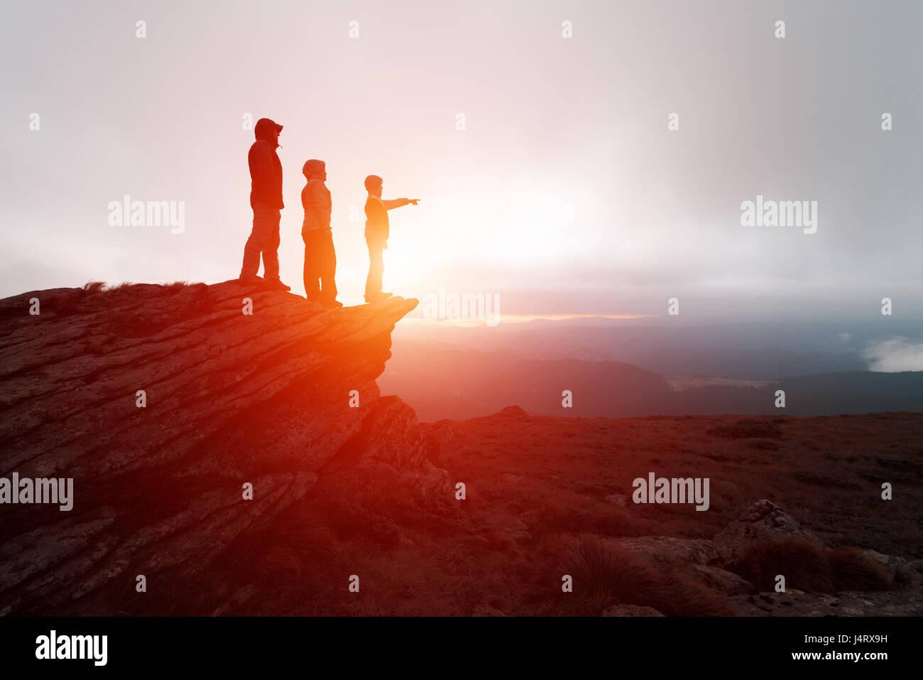Familie von Touristen, die am Rande der Klippe vor dem Hintergrund einer unglaublichen Berglandschaft. Abendzeit Stockbild