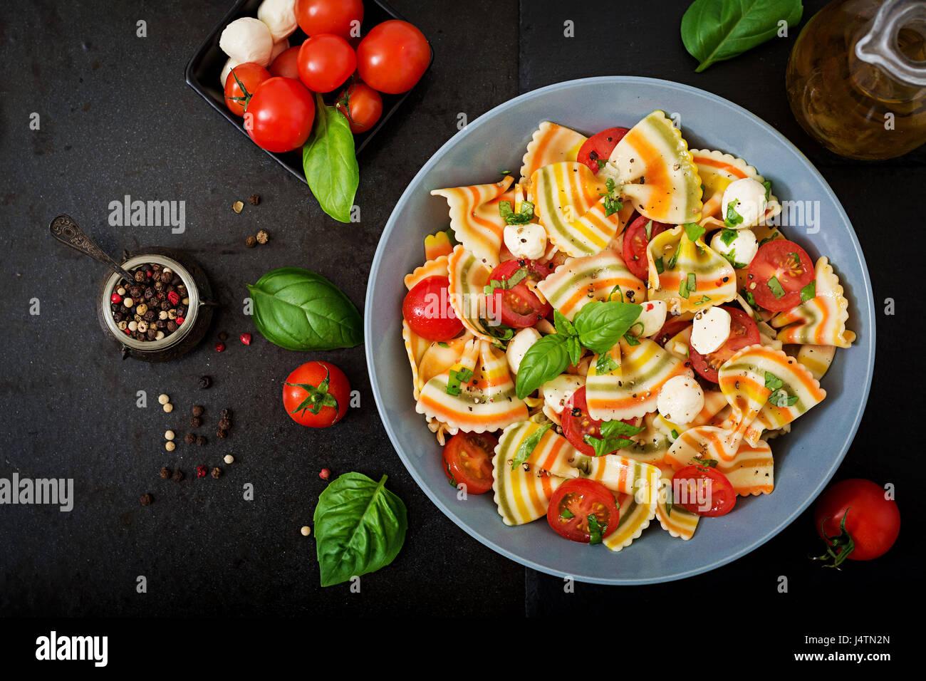 Nudeln, bunte Farfalle-Salat mit Tomaten, Mozzarella und Basilikum. Stockfoto