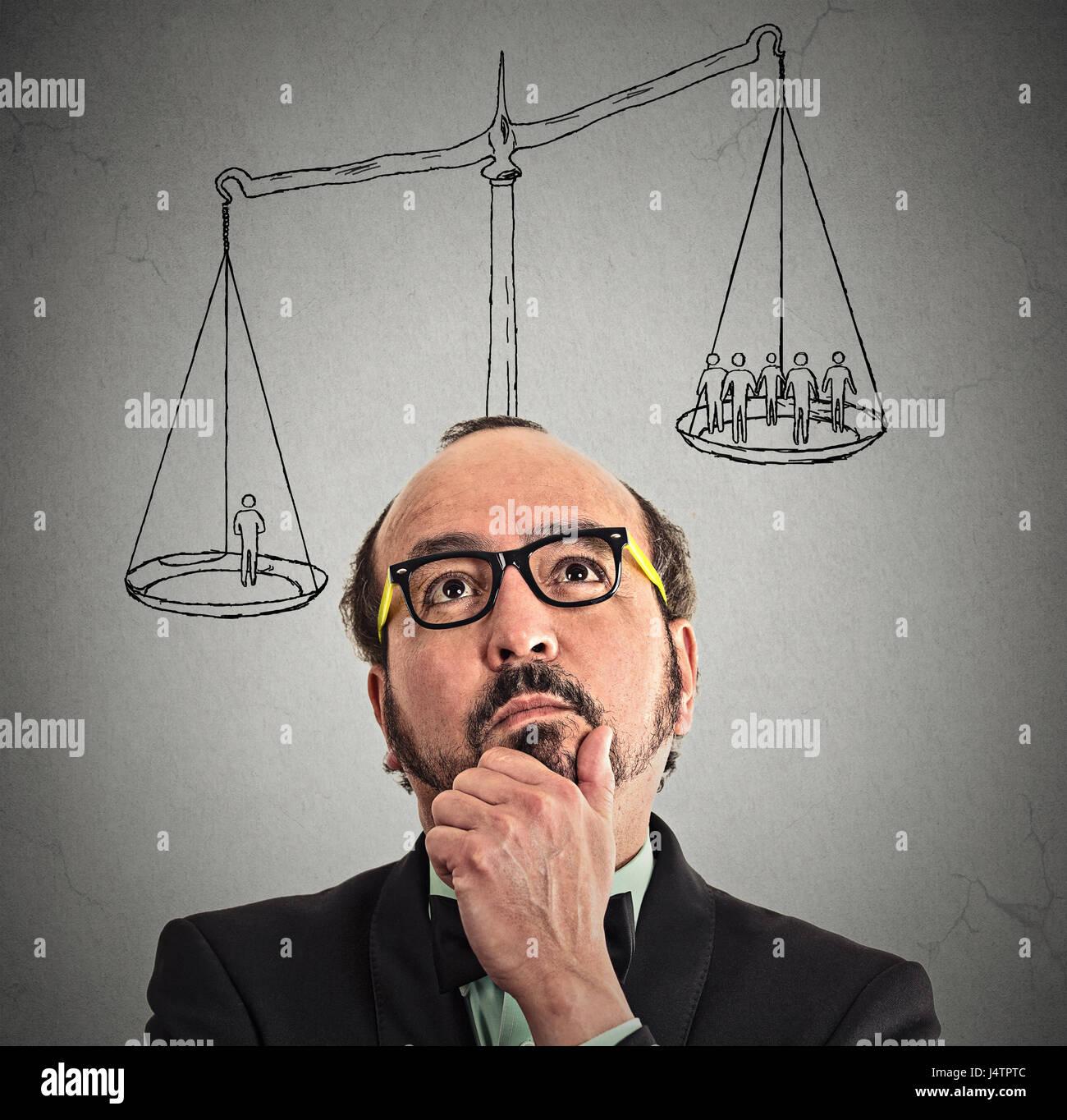 Geschäftsmann mit Skala über Kopf ein Mann mehr als Gruppe von Geschäftsleuten auf einem Gleichgewicht Stockbild