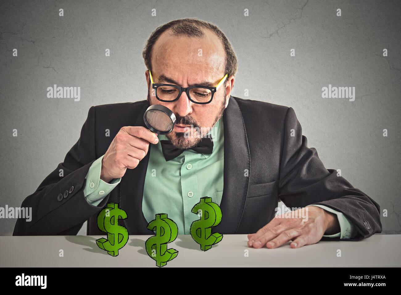 Pfennigfuchser. Blick durch die Lupe am Dollarzeichen Symbol auf Tisch Geschäftsmann isoliert graue Wand Office Stockbild