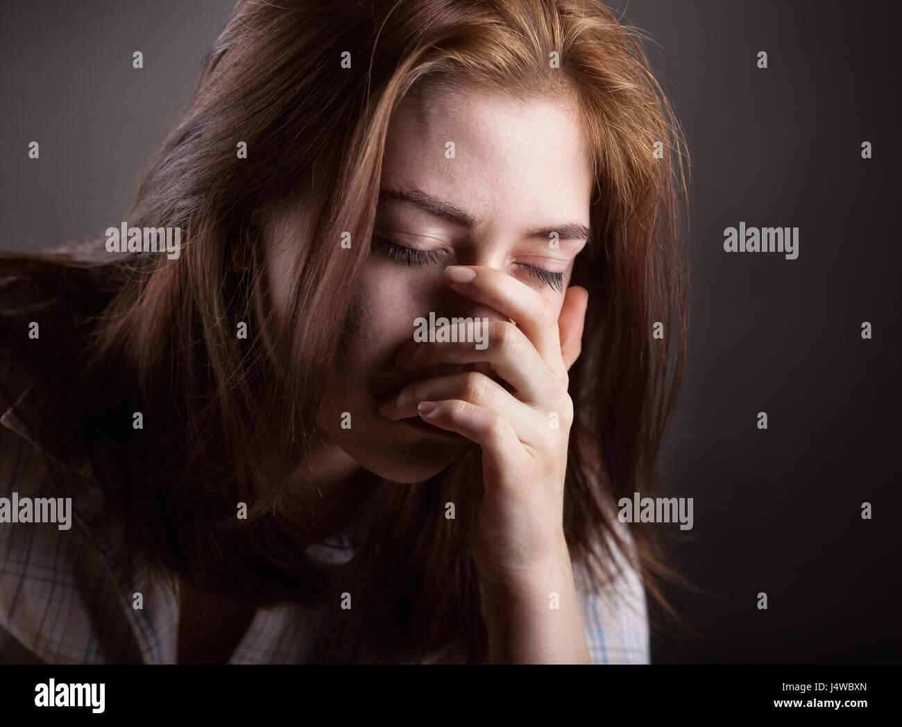 Weinende Frau auf dunklem Hintergrund Stockfoto