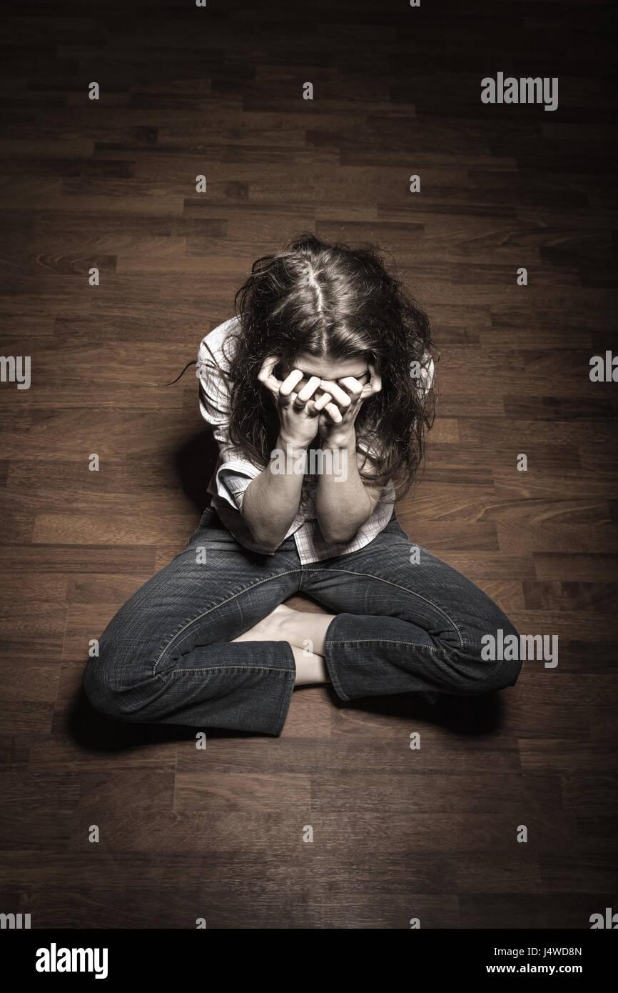 Traurige Frau sitzt alleine in einem leeren Raum Stockbild