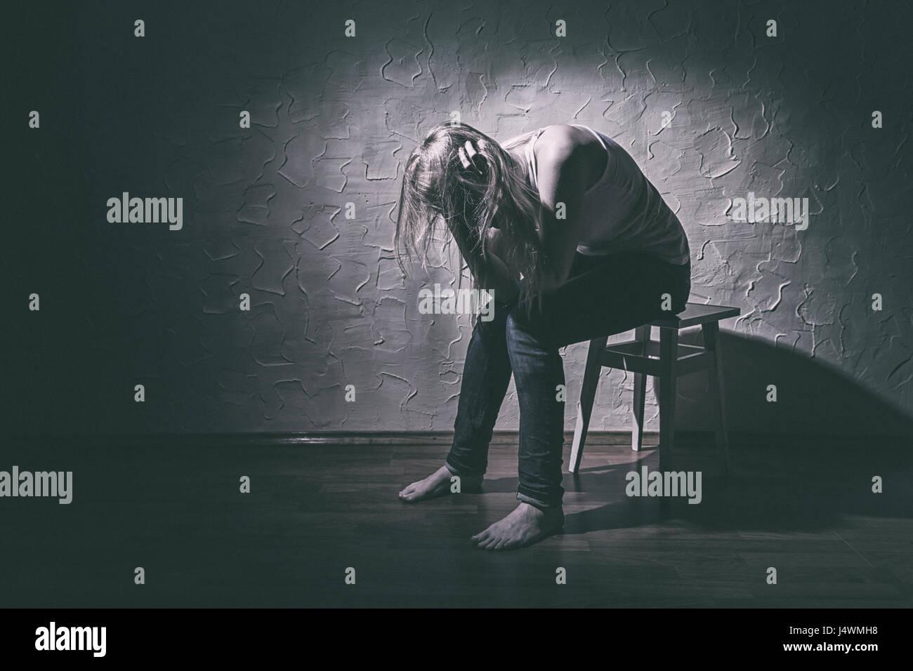 Junge traurige Frau sitzt alleine auf einem Stuhl in einem leeren Raum Stockbild