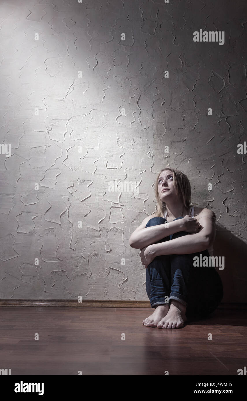 Junge traurige Frau sitzt alleine auf dem Boden in einem leeren Raum Stockbild