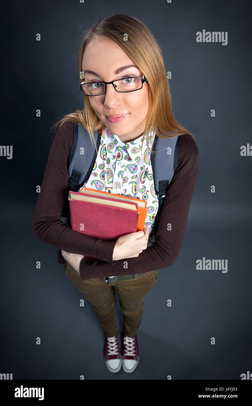 Niedliche Schulmädchen Buch hält und Blick in die Kamera Stockbild