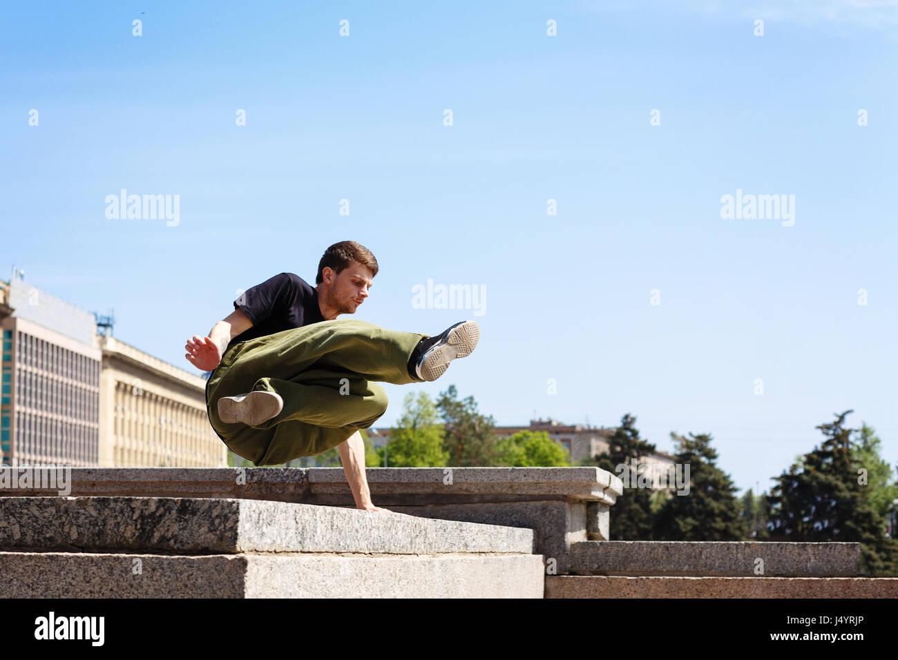 Junger Mann über die Mauer springen. Parkour im urbanen Raum. Sport in der Stadt. Sportliche Aktivität. Stockbild