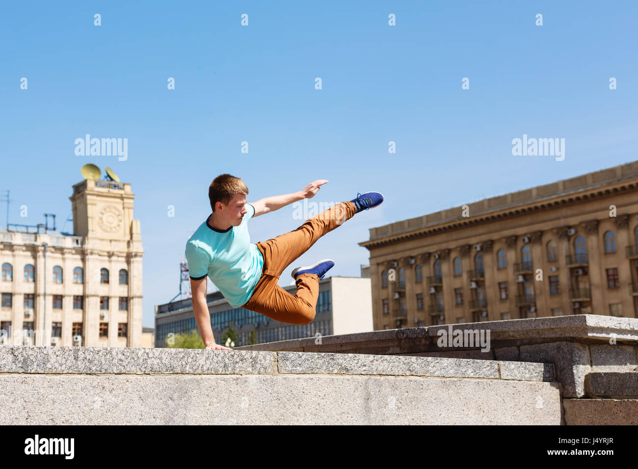 Junger Mann springt über die Mauer. Parkour im urbanen Raum. Sport in der Stadt. Sportliche Aktivität. Stockbild