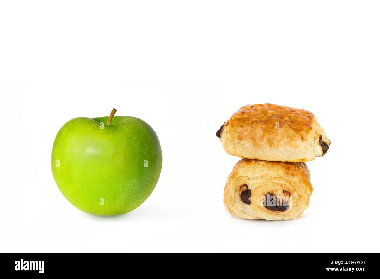 Schokoladencroissants und ein grüner Apfel auf weißem Hintergrund, gesund oder ungesund essen Wahl Konzept Stockbild