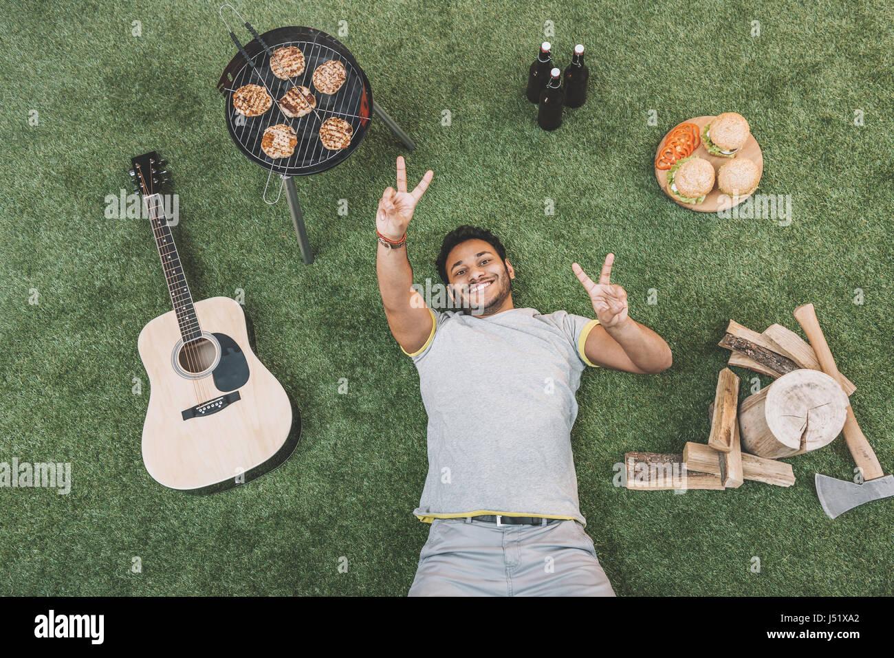 Draufsicht der glückliche junge Mann ruht auf dem Rasen mit Gitarre und Nahrung für Picknick Stockbild